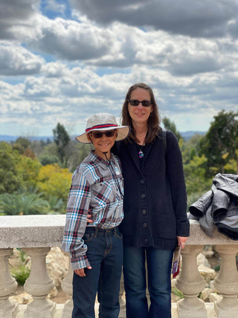 A white woman in sunglasses stands with her arm around her 12-year-old son, who is wearing a hat and sunglasses. Behind them is a low wall of cement pillars, and behind that, a vista of trees and distant hills.