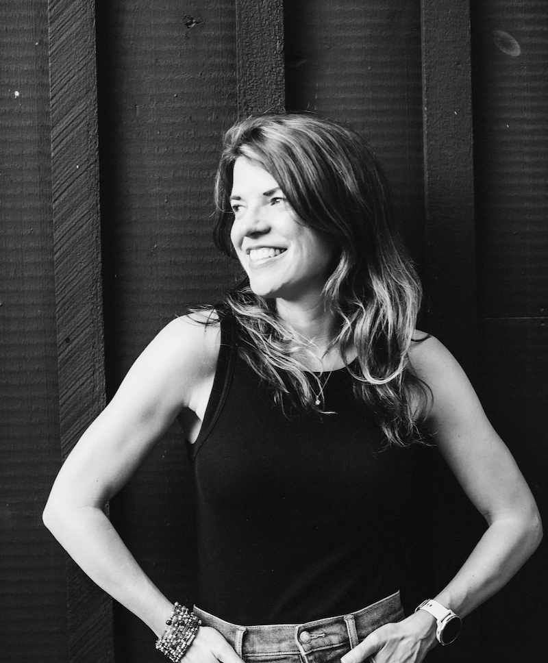 Black and white photo of the author with her hands on hips, looking to her right and smiling. She's wearing a dark tank top and jeans.