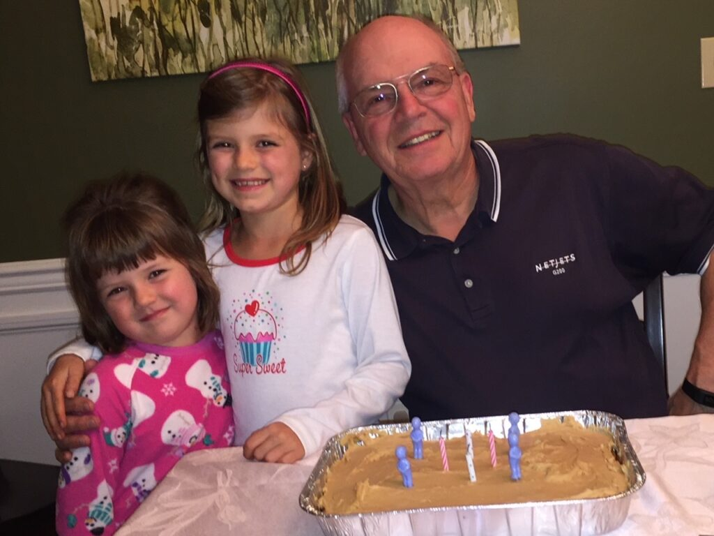 Photo of Jennifer Acker's father—a smiling, balding older white man with glasses—and her two young daughters, who both have brown hair and smiles