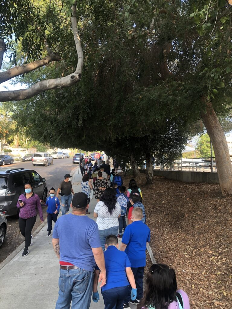 Parents and elementary school children wait in line beneath large trees outside a school campus