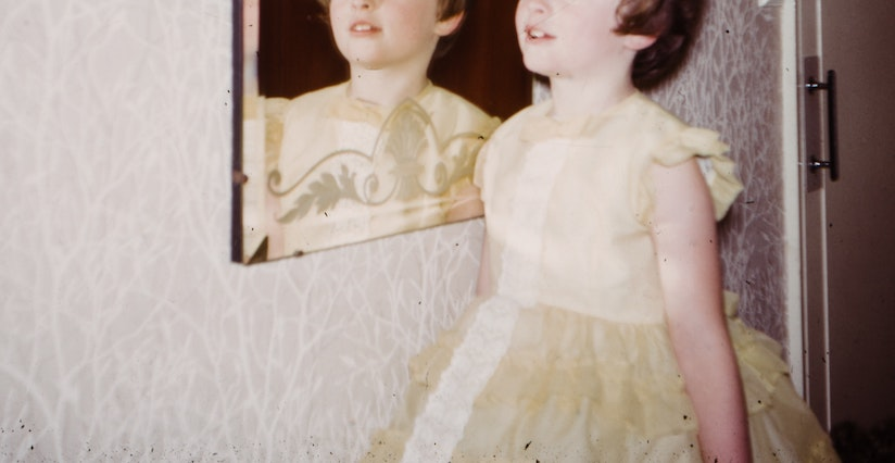 Young white girl with short brown hair and a frilly yellow dress standing next to a mirror