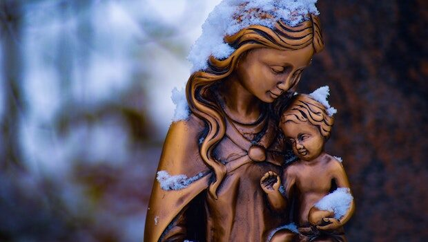 Gold-hued, snow-dusted statue of a mother holding an infant