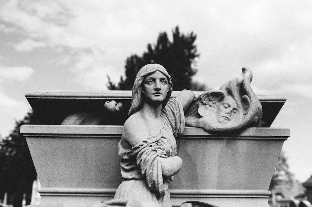 Stony statue of a woman in front of a coffin. The coffin is slightly open and an angel is climbing out.
