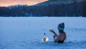 A thin white woman wearing a bikini top and a knit beanie stands chest-deep in a partially frozen lake, raising a glass. A bottle of alcohol is next to her, and the sun is setting behind mountains in the background.