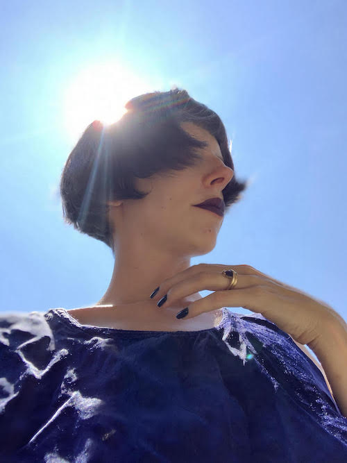 White woman with dark bobbed hair, dark lipstick, and dark blue fingernails. Her face is partially obscured by her hair. The sun shines brightly behind her.