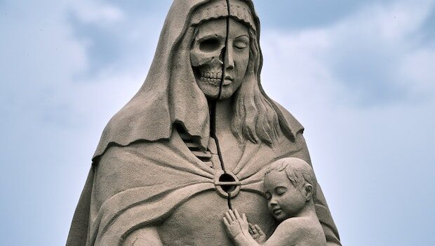 Stony statue of a woman holding a child; half her face appears as a skull