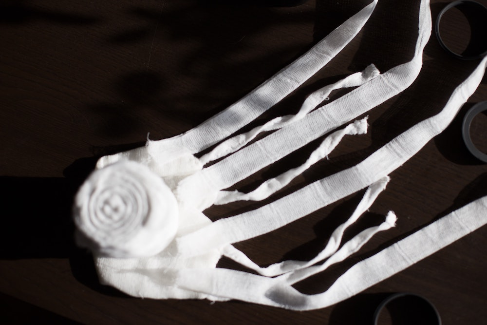 A roll of white bandages unraveling against a black backdrop