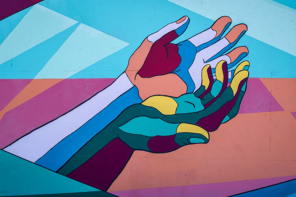 Mural depicting two outstretched hands in bright blues, purples, and greens, with yellow and peach highlights